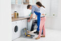 Woman looking at male worker repairing oven young in overall in kitchen Royalty Free Stock Images