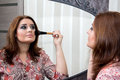 Woman looking in the mirror and applies himself blush. Royalty Free Stock Photo