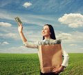 Woman looking at one hundred dollars smiley successful holding paper bags with money and over blue sky and green field Stock Photos