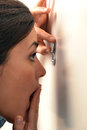 Woman looking out through the peephole Royalty Free Stock Photo