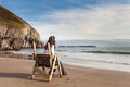 Woman looking out to sea on chair at the shore Stock Photos