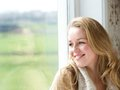 Woman looking outside through window close up portrait of a smiling Stock Photography