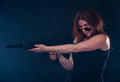 Woman looking over her glasses while aiming a gun Stock Photography