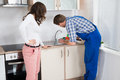 Woman Looking At Plumber Fixing Sink Royalty Free Stock Photo