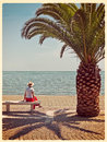 Woman looking at sea, sitting under palm tree in sunshine. Filte Royalty Free Stock Photo