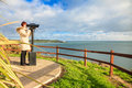 Woman looking through sightseeing binoculars overlooking the ocean Stock Photos