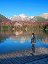 Woman looking at strbske pleso high tatras autumn view portraying elegant standing on wooden pier tarn with massive peaks of in Royalty Free Stock Photo