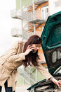 Woman looking under car hood on phone Royalty Free Stock Image