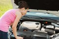 Woman looking under hood car shocked young at engine Stock Image