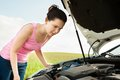 Woman looking under hood car shocked young at engine Royalty Free Stock Image