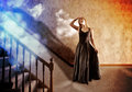 Woman looking up at bright light of hope a is floating and stairs to a blue with clouds around her for a faith or fantasy concept Stock Image