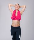 Woman looking up with hands behind head portrait of a beautiful young relaxing after exercise workout on gray background Royalty Free Stock Photos