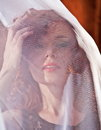 Woman looking through veil portrait of beautiful young with face obscured by white Royalty Free Stock Image