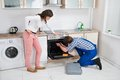Woman looking at worker repairing oven male appliance in kitchen room Stock Photography