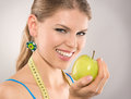 Woman loosing weight close up of happy diet by eating healthy food young attractive caucasian female model with green apple and Stock Photos
