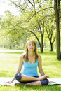 Woman in lotus yoga pose outside female fitness instructor outdoor at spring park Royalty Free Stock Images