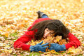 Woman loving autumn season on day surrounding lots of yellow leaves and smiling relaxed happy girl lying down and enjoying fall in Royalty Free Stock Photo