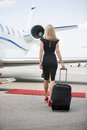 Woman with luggage walking towards private jet rear view of wealthy at airport terminal Royalty Free Stock Photography