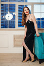 Woman in luxury black dress with slit full body portrait of beautiful young hollywood make up and hair style Stock Image