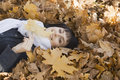 Woman lying on autumnal leaves portrait of a smiling in park Royalty Free Stock Image