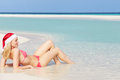 Woman lying on beach wearing santa hat relaxing Stock Photography