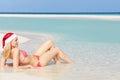 Woman lying on beach wearing santa hat relaxing Stock Photography