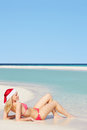 Woman lying on beach wearing santa hat relaxing Royalty Free Stock Photography