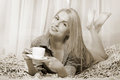 Woman lying at the bed and drinking coffee and smiling sepia toned Stock Images