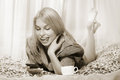 Woman lying at the bed and smiling using mobile phone sepia toned Royalty Free Stock Photography