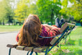 Woman lying on a bench in the park Royalty Free Stock Photo
