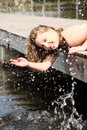 Woman is lying on the bridge and splashing water. Stock Image