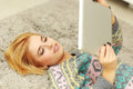 Woman lying on the carpet with tablet computer young happy Royalty Free Stock Photos
