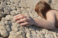 Woman lying on cracked land with focus on hand Royalty Free Stock Photography