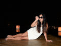 Woman lying on decking glamorous young smiling asian wearing sun glasses and white dress wooden with background of city at night Stock Photos