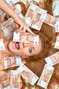 Woman lying down with many cash money five thousand russian rubl surprised young rubles notes in hand looking at the camera Stock Images