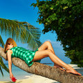 Woman lying down on a palm tree at tropical beach Stock Images