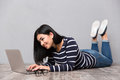 Woman lying on the floor and using laptop Royalty Free Stock Photo