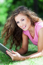 Woman lying on grass with digital tablet smiling Stock Photography