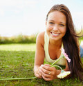 Woman lying on grass field while holding a flower Stock Image