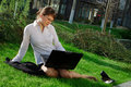 Woman lying on grass with laptop Royalty Free Stock Image