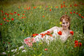 Woman lying in grass among poppies Stock Images
