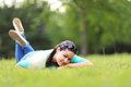 Woman lying on the grass at summer sunset. Royalty Free Stock Photo