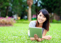 Woman lying on grass with tablet computer the Royalty Free Stock Photos