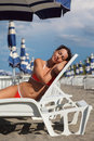 Woman lying on lounger under beach umbrella Stock Photography