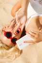 Woman lying on sandy beach using cell phone Royalty Free Stock Photo