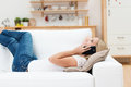 Woman lying on the sofa chatting on the phone in casual jeans in her living room her mobile with her feet up Stock Images