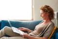 Woman lying on sofa with laptop smiling Royalty Free Stock Photo