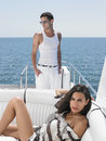 Woman lying on sofa with man standing in yacht portrait of sensuous young women men Royalty Free Stock Image