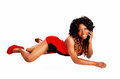Woman lying on stomach a pretty jamaican in a red short dress and long curly hair the floor isolated for white background Royalty Free Stock Photography