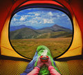 Woman lying in a tent with coffee ,view of mountains and sky Royalty Free Stock Photo